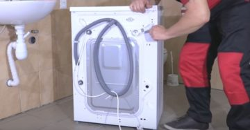мастер устанавливает стиральную машину